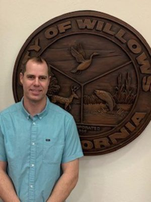 Hilgard Muller in front of the Glenn County seal. headshot